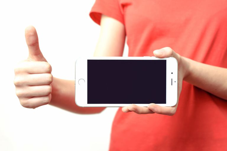 person holding an iPhone up in one hand make the thumbs up sign with the other