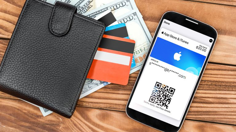 An iPhone with the iOS Wallet app open showing the App Store and iTunes Pass next to a wallet full of cash and credit cards.