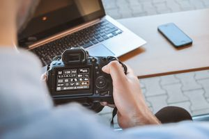 Someone using a DSLR camera with a laptop and iPhone in the background.