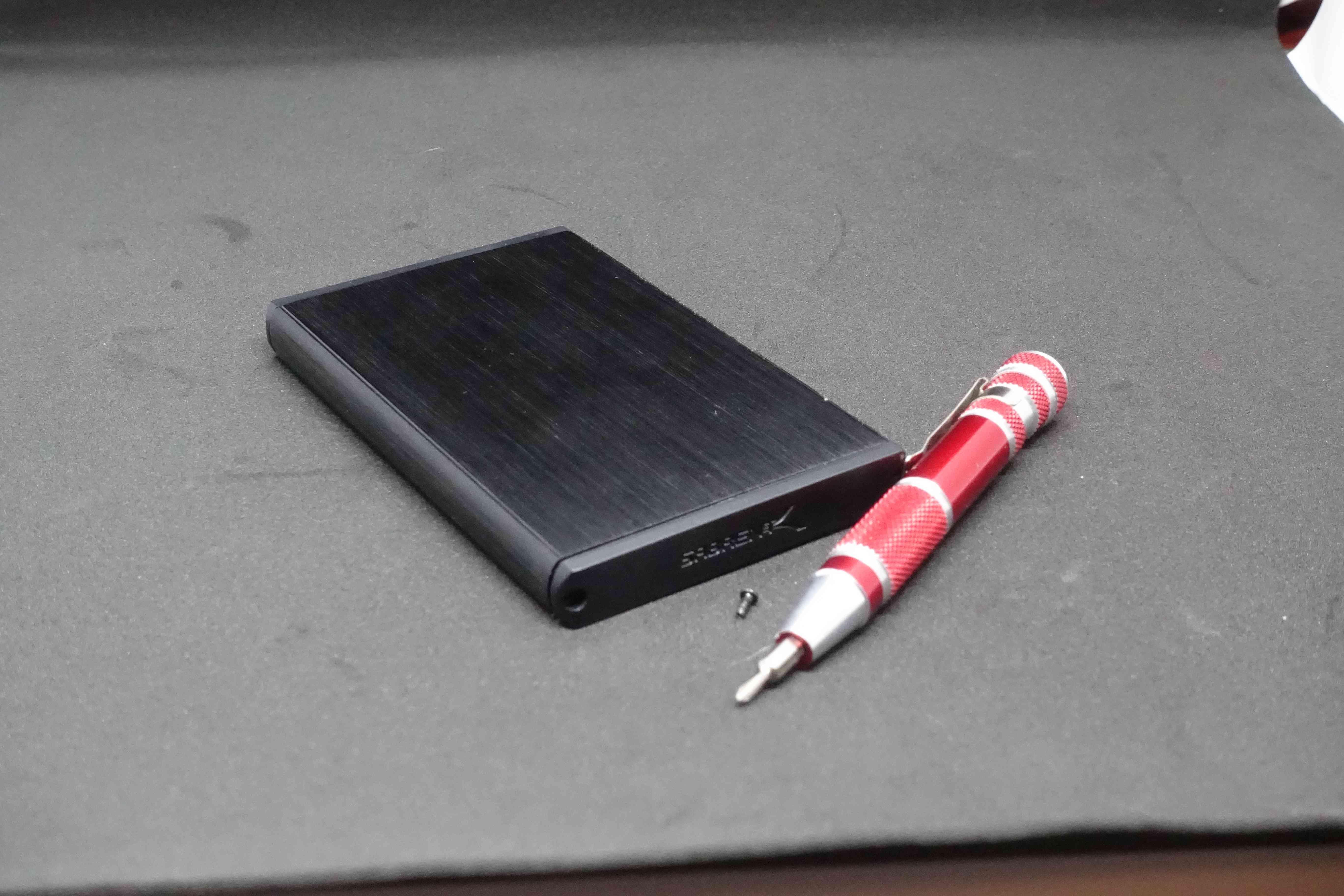 An external hard drive with a screwdriver.