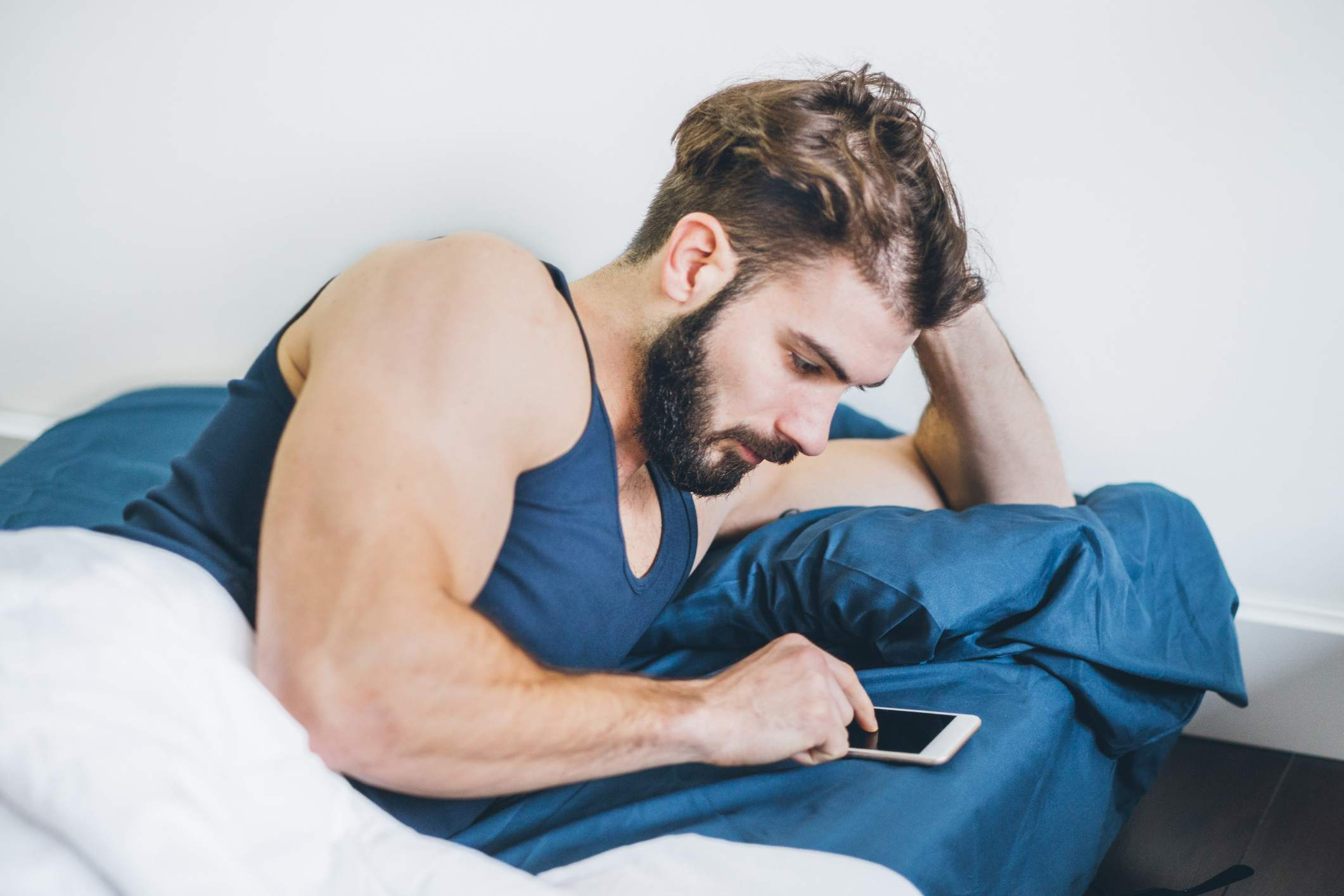 Man in bed texting on phone