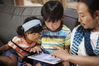 A parent with two children sitting on a grey sofa, looking at digital tablet.