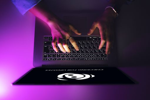 Birds-eye view of a woman's hands typing on a laptop with the Discord connection logo on the screen.