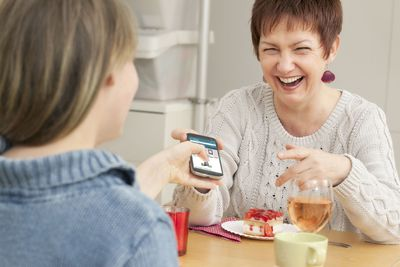 A mother hands her child a phone after setting Amazon parental controls.