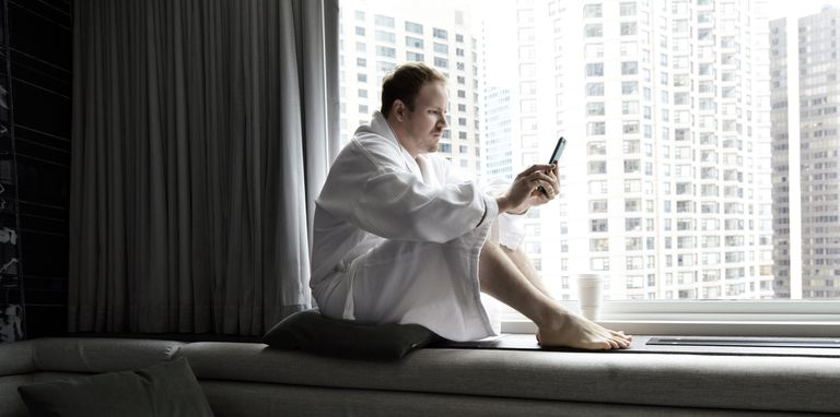 Man sitting in robe next to clear glass window
