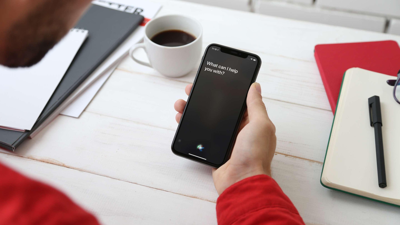 A man using Siri on an iPhone.