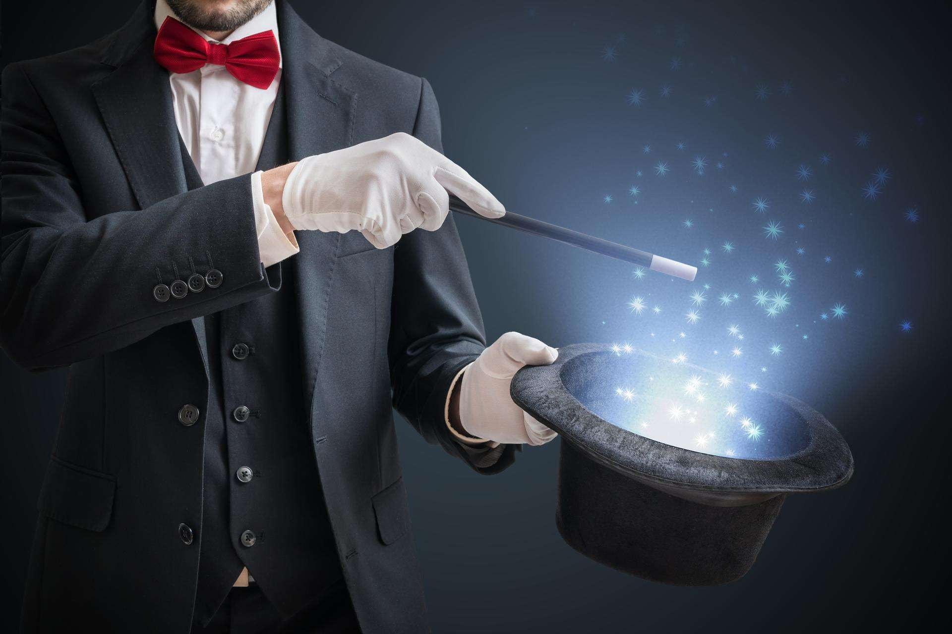 Magician tapping his hat with a wand