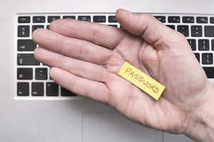 A hand holding a small piece of paper with the password written on it.