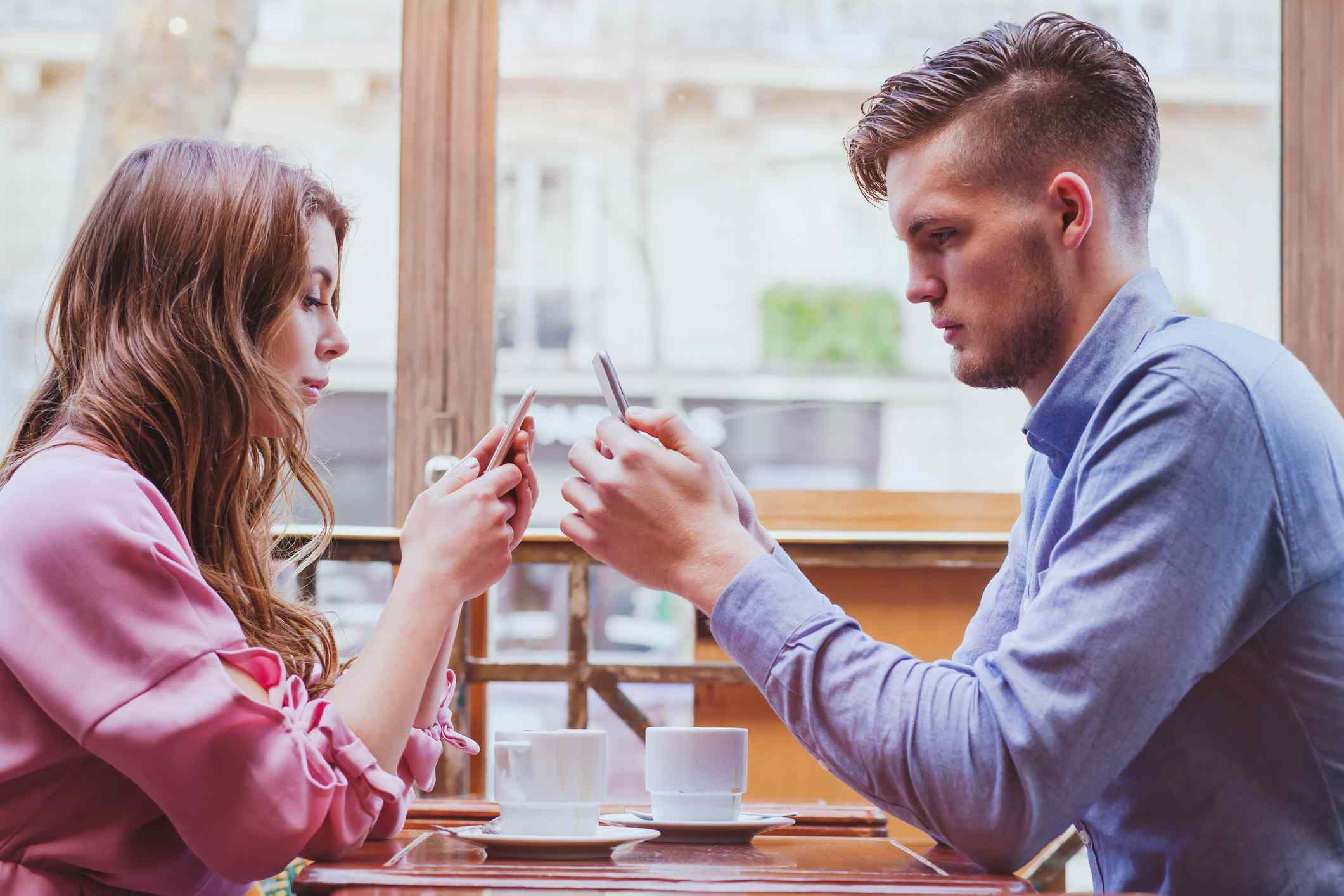 A couple at a restaurant ignoring each other while they use their phones.
