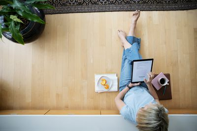 View from above barefoot woman working from home, using digital tablet on floor
