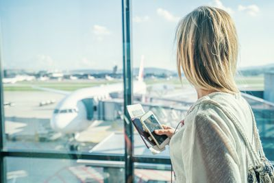 Someone looking out a window at an airport holding a smartphone and a passport.