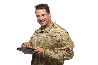 Soldier smiling and holding a tablet in his hands.
