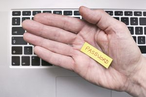Hand holding note saying Password with keyboard on the background