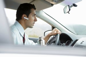 Man in car with bluetooth earpiece