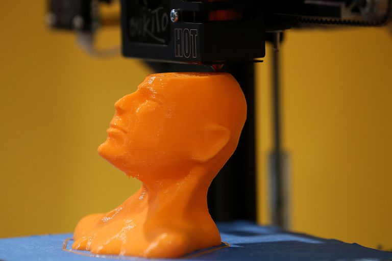 a 3d printer building a human head in orange plastic