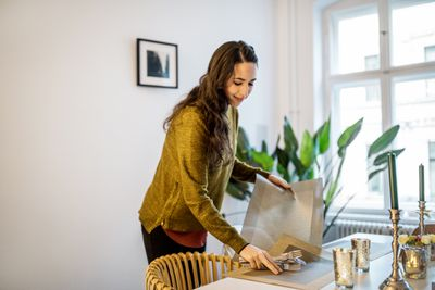 Home owner organizing a dining room and smiling