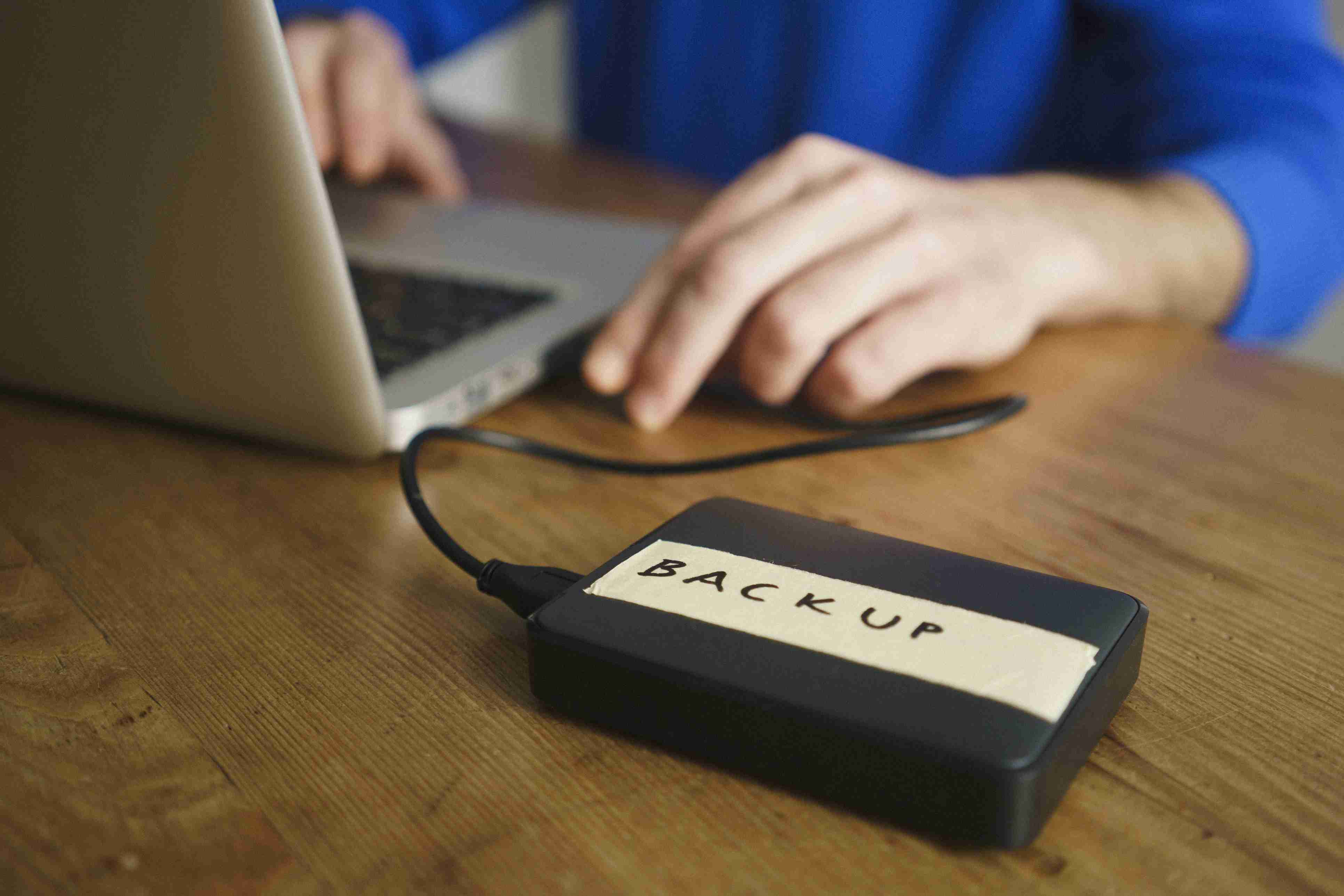 Midsection of man using laptop with backup label on external hard disk drive at table