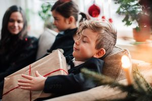 Young boy very happily holding a Christmas gift