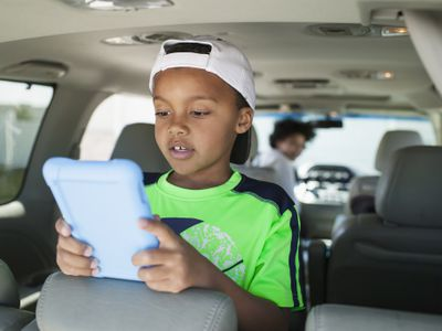 Boy with tablet in minivan with mom driving