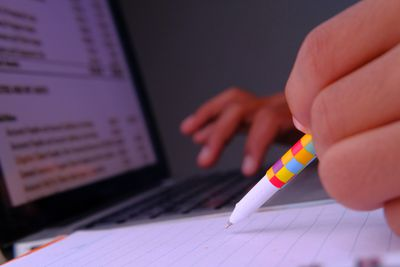 Image of person writing on note pad and working on laptop