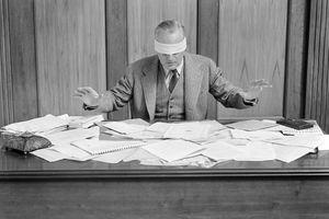 Blindfolded Businessman At Desk Covered With Paper