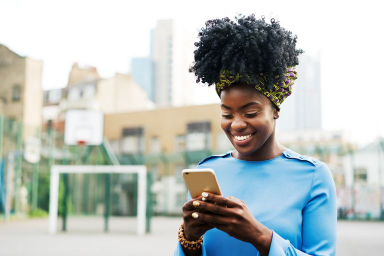 Woman using iphone in city downloading free ringtones
