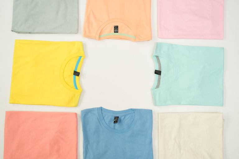 An image of colored T-shirts folded neatly