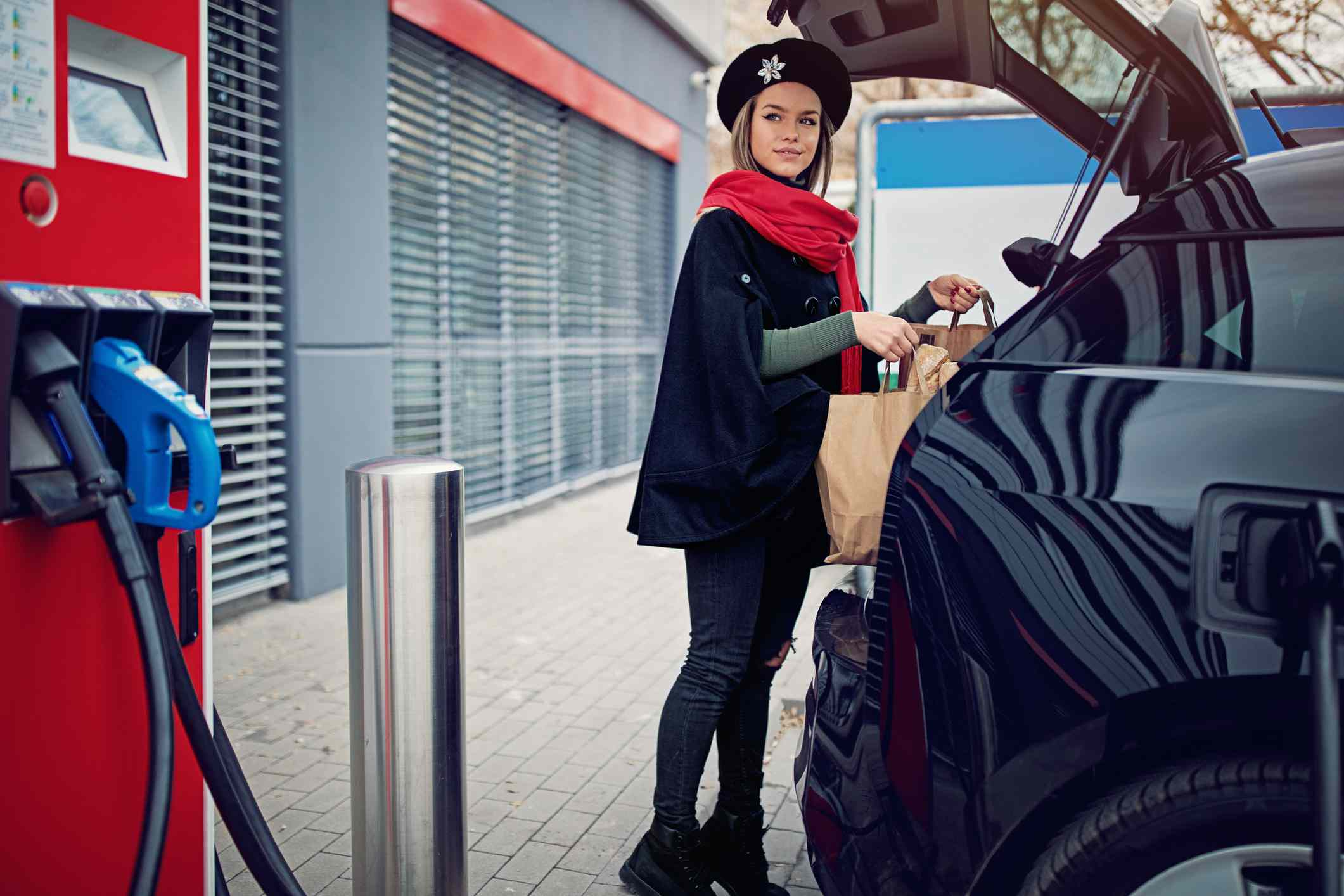 Woman loading groceries into EV at supermarket charging station,