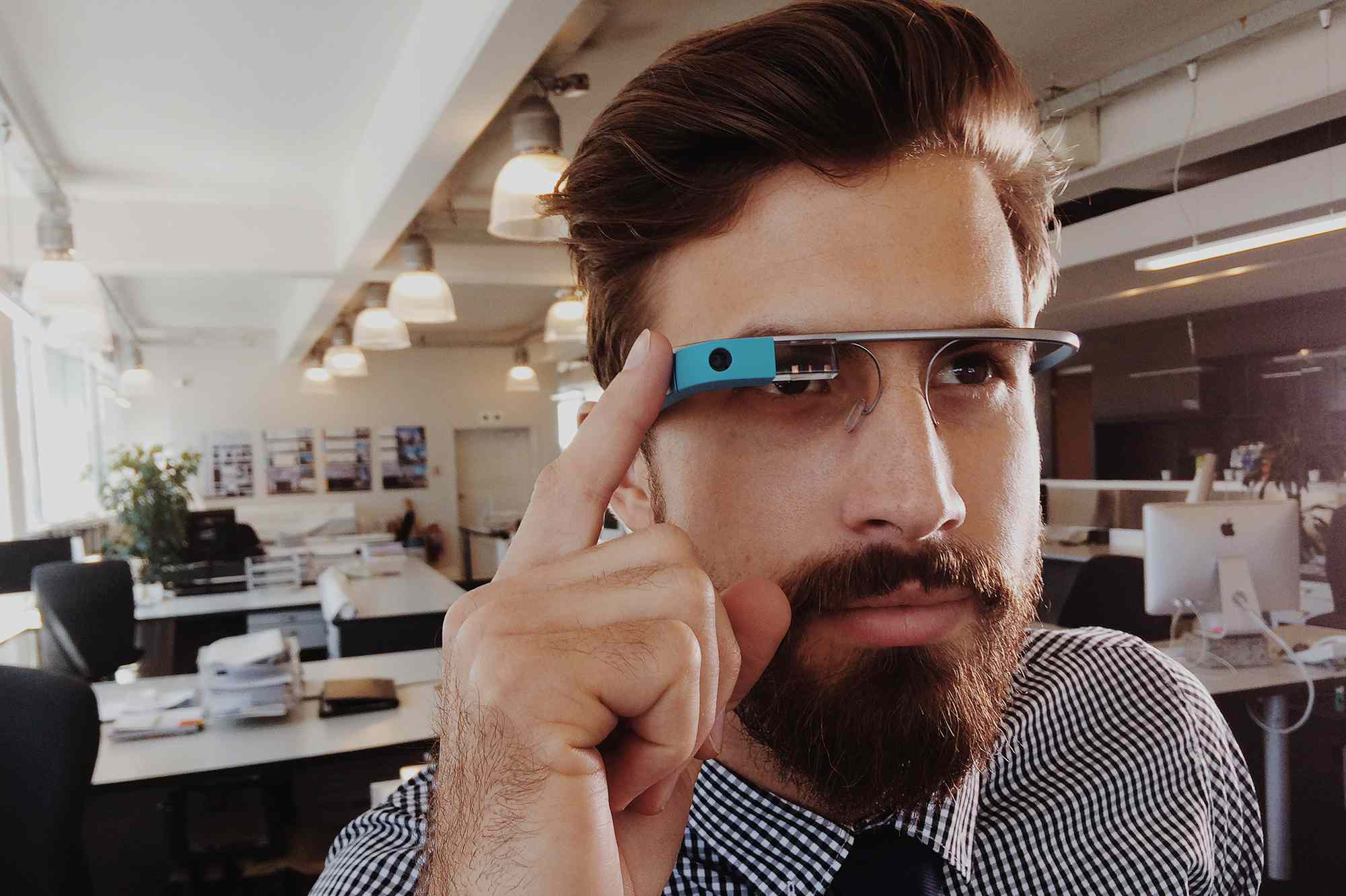 Google glass being worn by a man in a open office setting