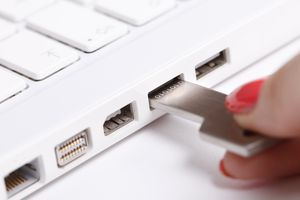 A USB security key is inserted into a laptop.