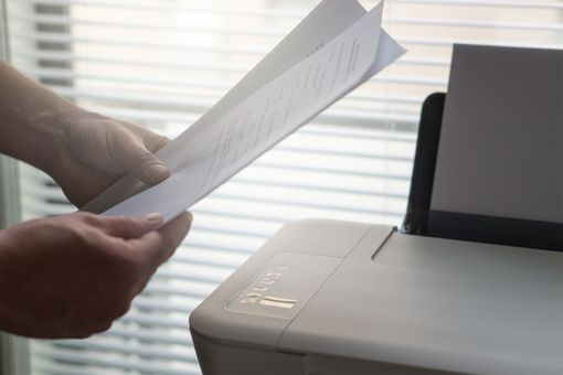 A person holding a printed page next to a printer.