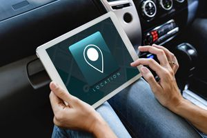 A person sitting in a car with a tablet uses a GPS location app.