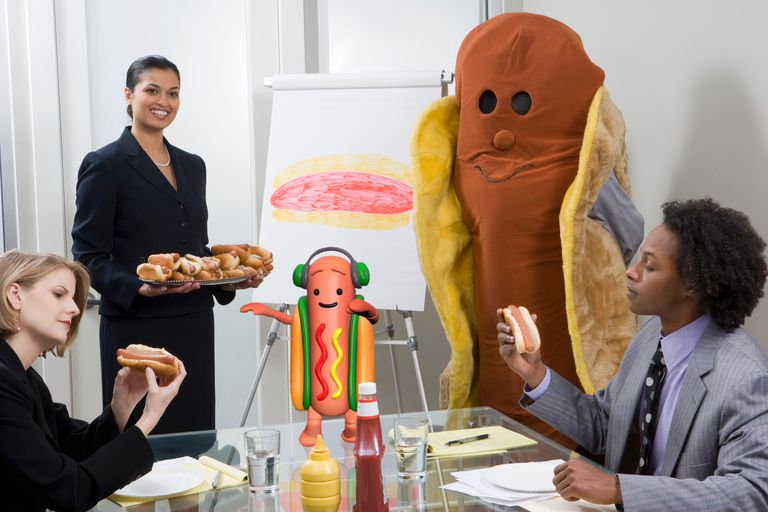 People eating hotdogs in a conference room with the dancing hot dog on the desk