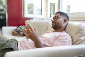 A man sitting on a sofa smiling at his smartphone