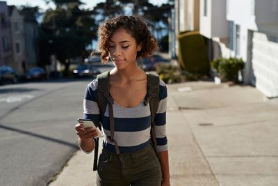 Woman walking on steep road and looking at smartphone