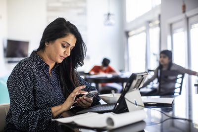 A woman looking at her smartphone while sitting at a desk