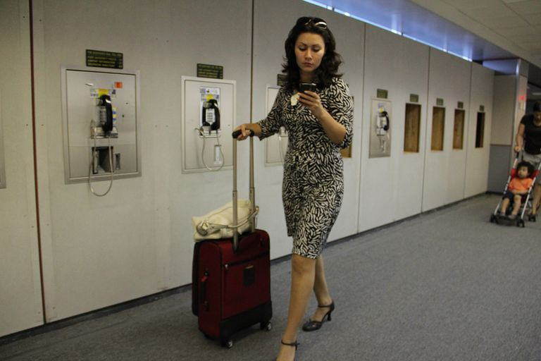 Business traveler walking with suitcase on her phone