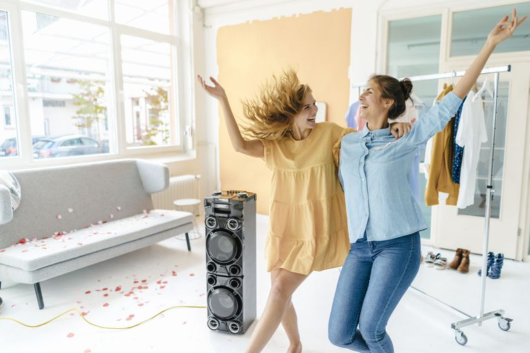 Two women dancing to music from a speaker.