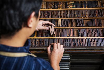 Rear view of man arranging alphabets and numbers letterpress at workshop