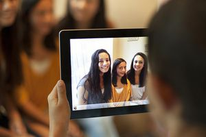 Boy Taking Picture of Sisters with Digital Tablet