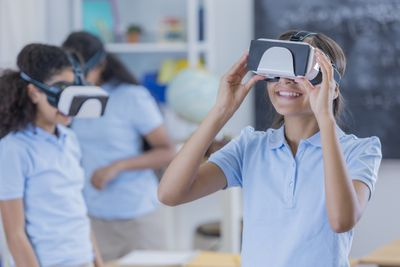 Group of students using virtual reality glasses as school.