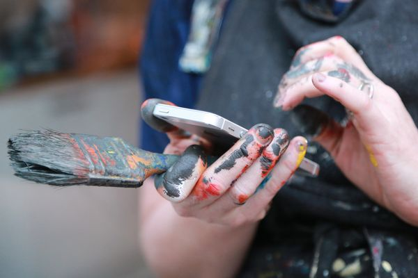 Someone using an iPhone holding a paint brush.