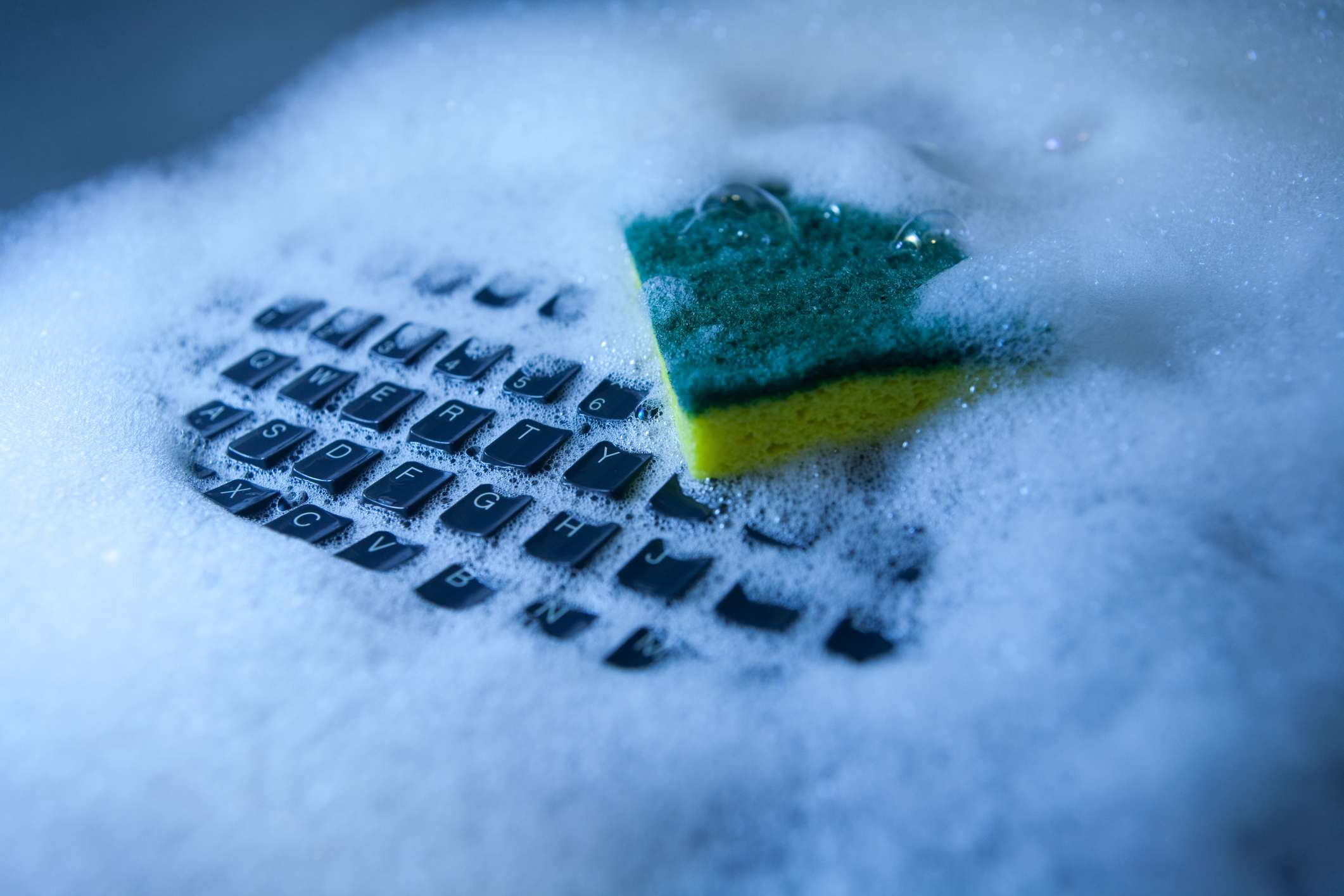 Photo of a computer keyboard under soapy water