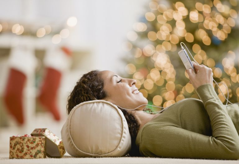 A woman listening to Christmas music on her phone.