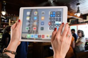 A woman holding an iPad with the Control Center open