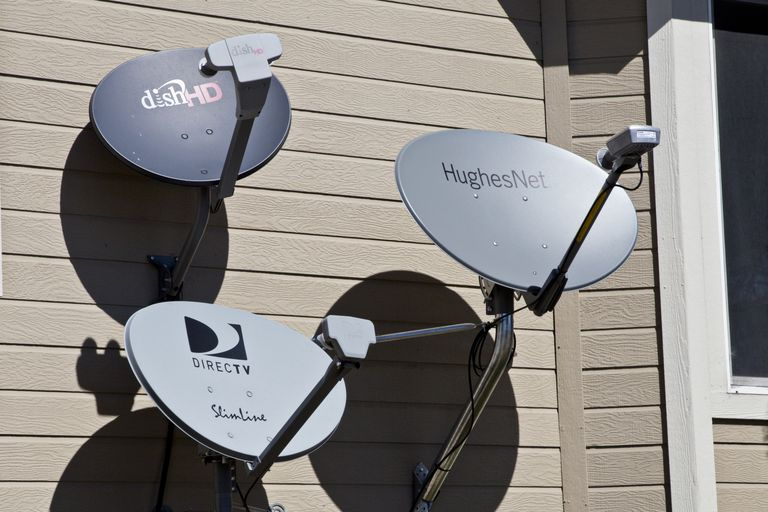 Several competing satellite services mounted on the side of a home