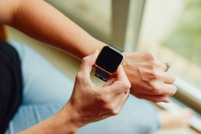 A woman's wrist with a close up of a smartwatch