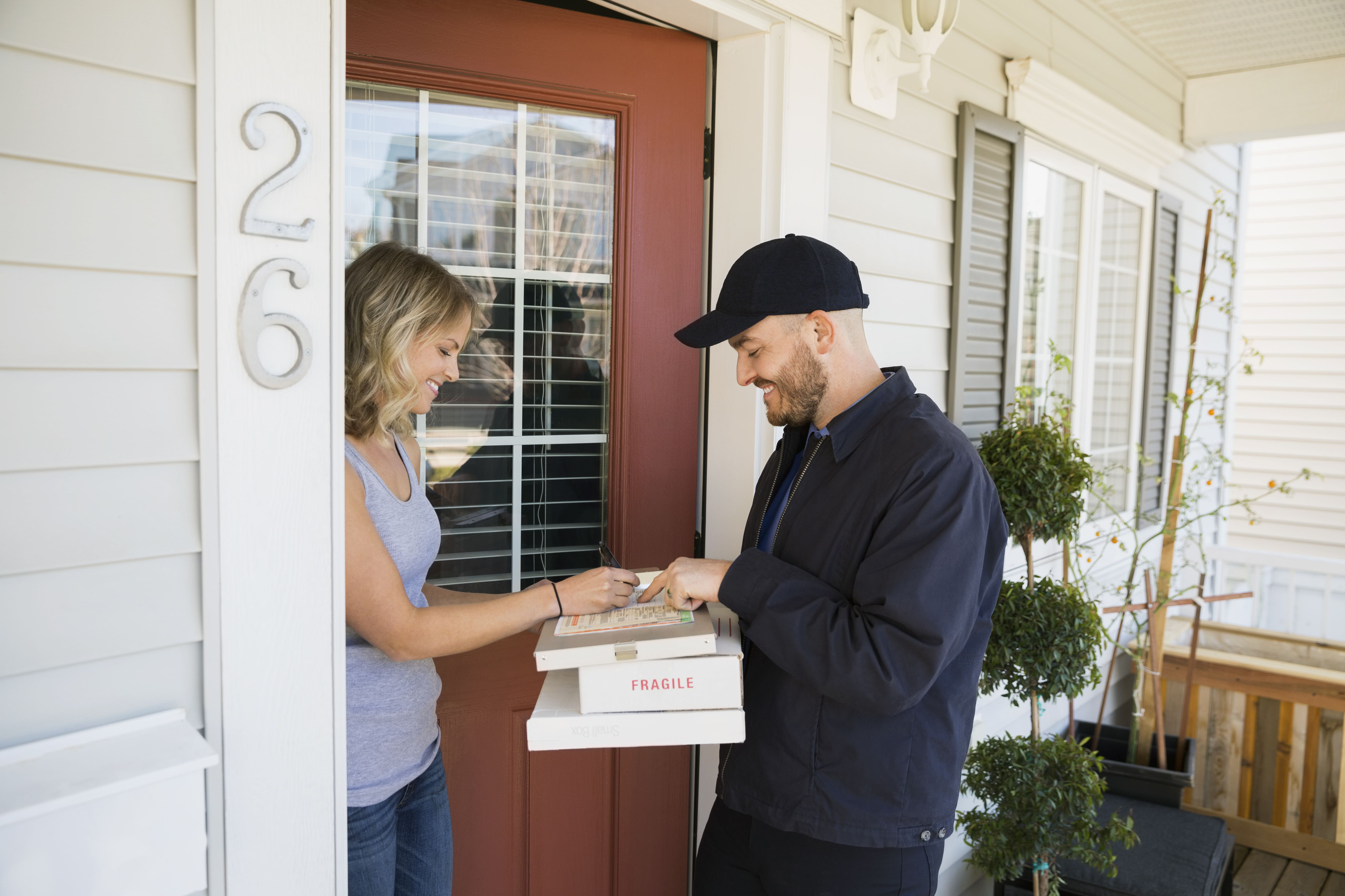 Woman signing for delivery at front door