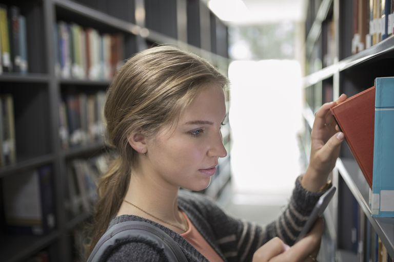 Close up female college student using cell phone and reaching for book on bookshelf in library