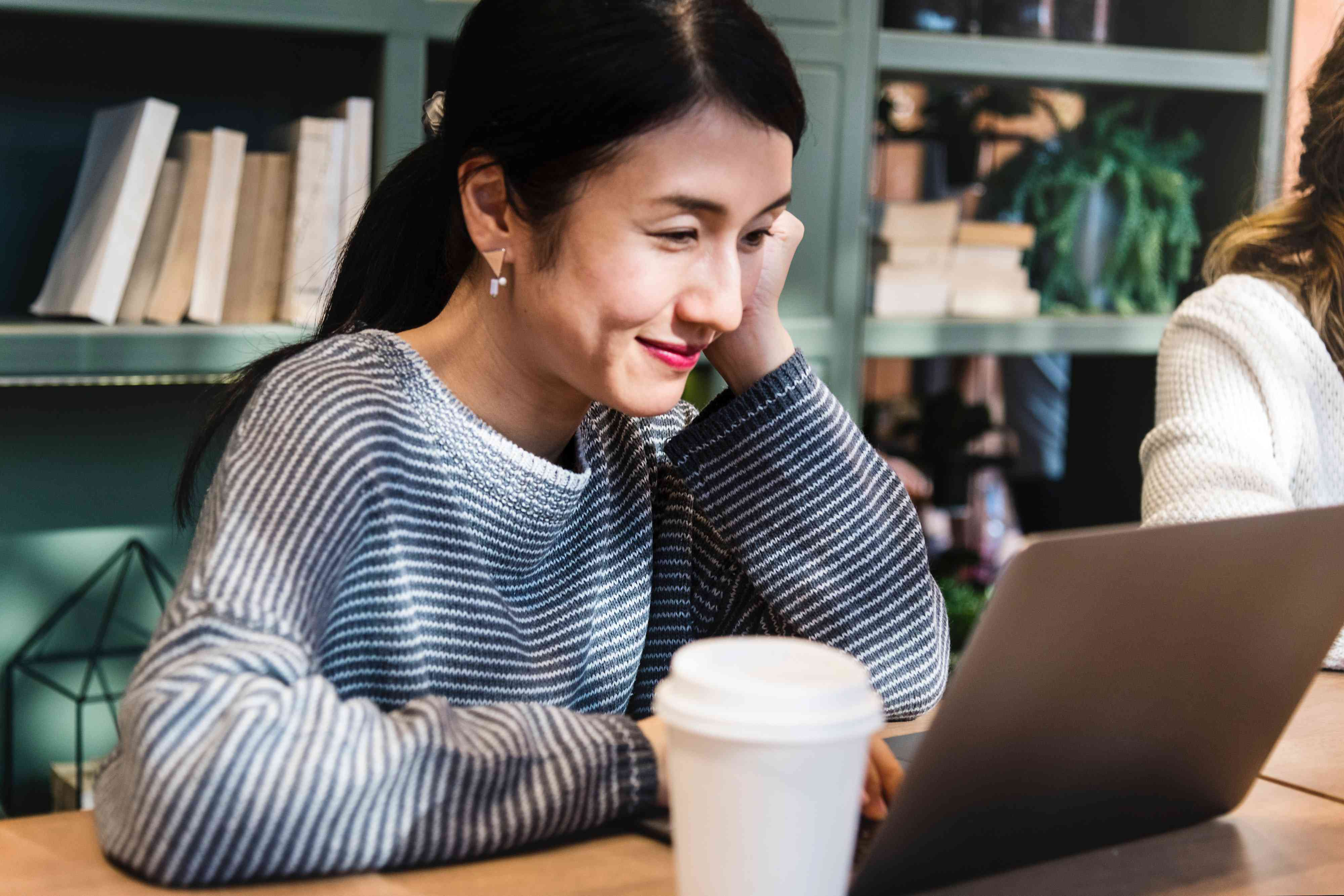 Smiling, relaxed woman using laptop